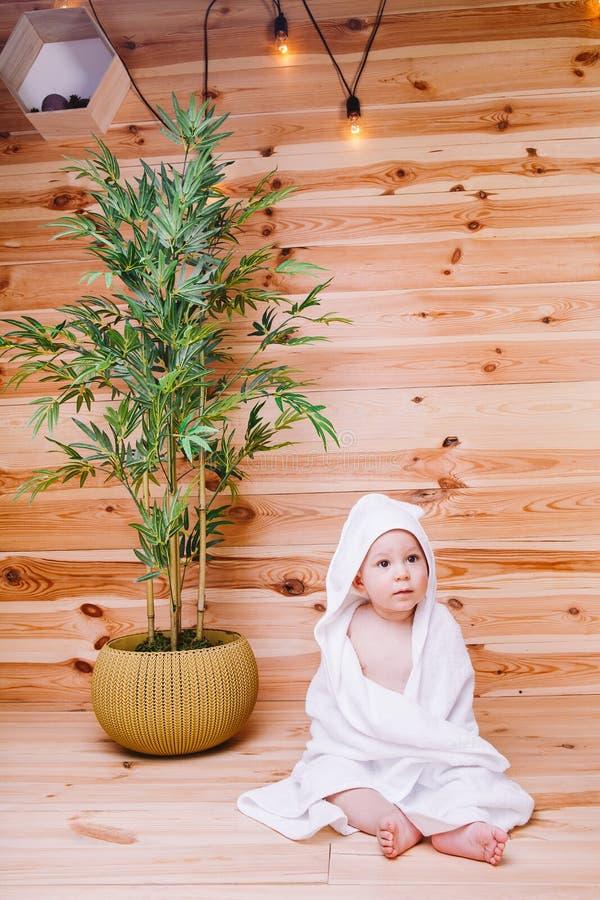 Das Baby eingewickelt in einem weißen Tuch, das auf hölzernem Hintergrund nahe einem Bambusbaum im Topf sitzt lizenzfreie stockfotos