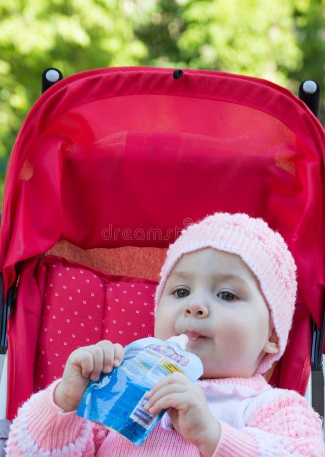 Das Baby isst ein Püree von einem Supermarkt stockbild