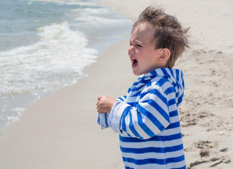 Das Baby ist auf dem Strand vor dem hintergrund des Strandes in einer gestreiften Robe und dem Schauen in den Abstand schreiend lizenzfreie stockfotos