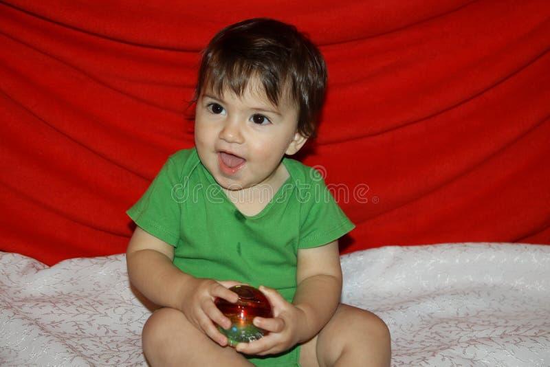 das Baby sitzt das Spielen und lacht einen Glasweihnachtsball glücklich, halten stockbilder