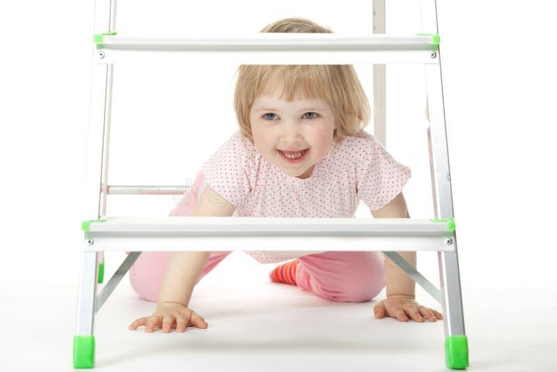 Das Baby sitzt unter einem Stepladder stockbild