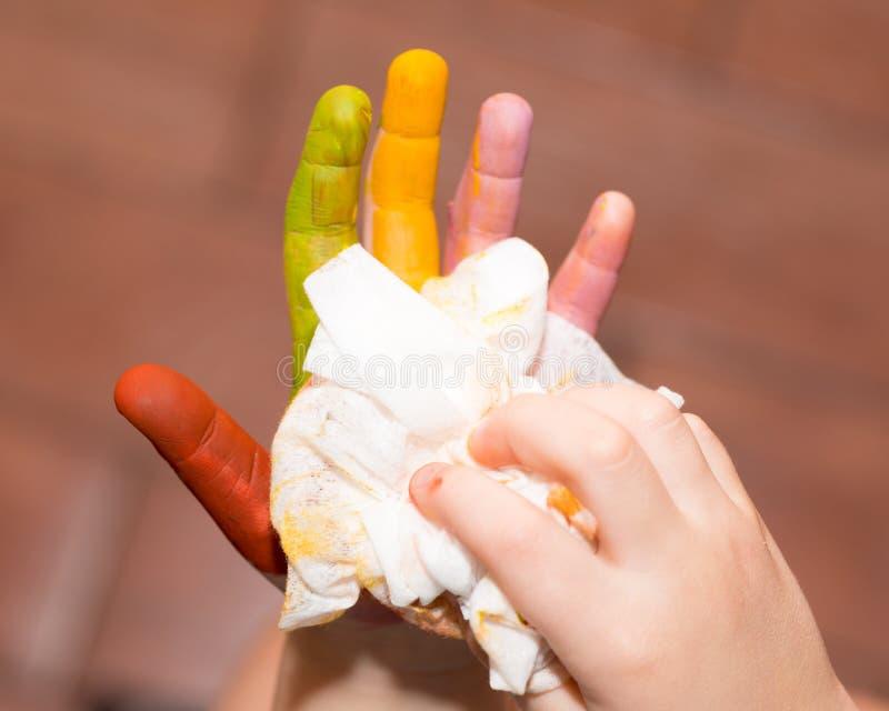 Das Baby wischt ihre Hände mit einer Serviette ab stockbild