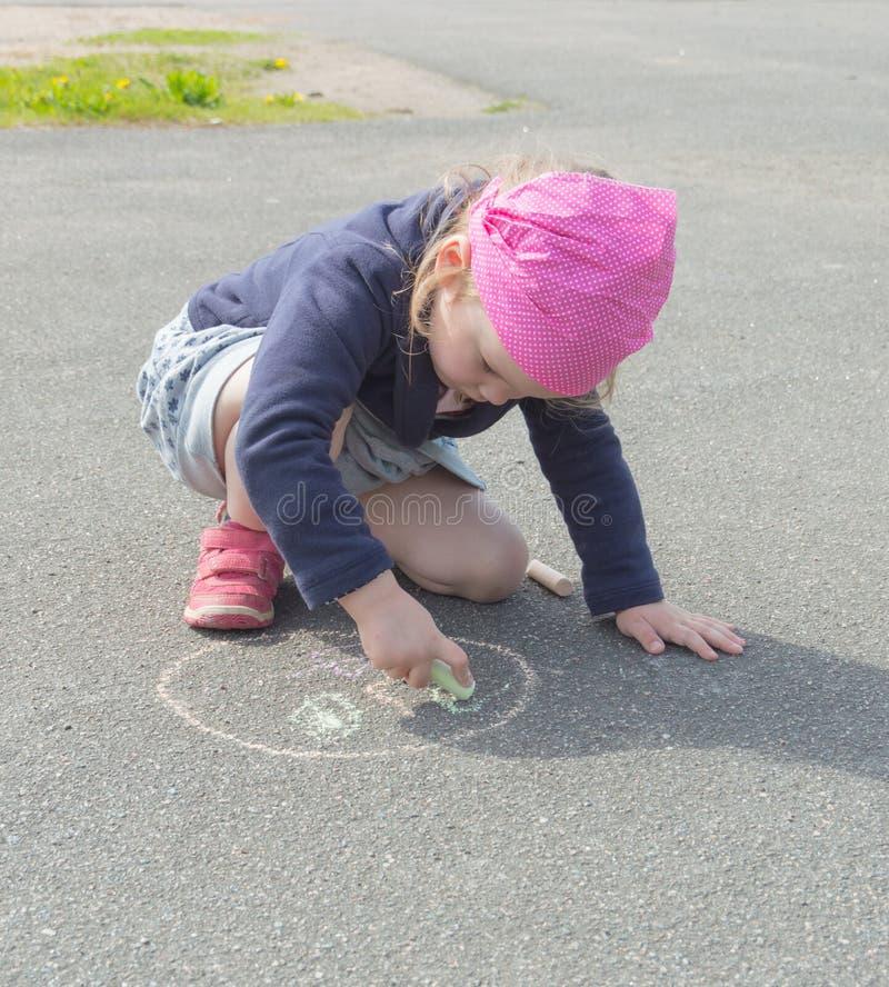 Das Baby zeichnet auf die Pflasterung in einem Kreis lizenzfreies stockbild