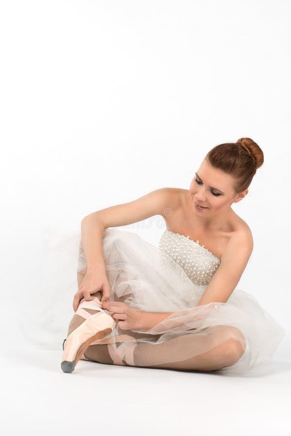 Das Ballerinakleid sitzt auf einem Boden und bindet rosa pointes lizenzfreie stockfotos