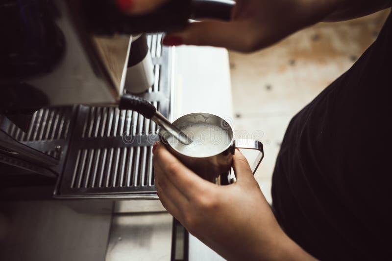Das barista macht gekochte Milch Er benutzt spezielle Kaffeemaschine für sie lizenzfreie stockfotografie