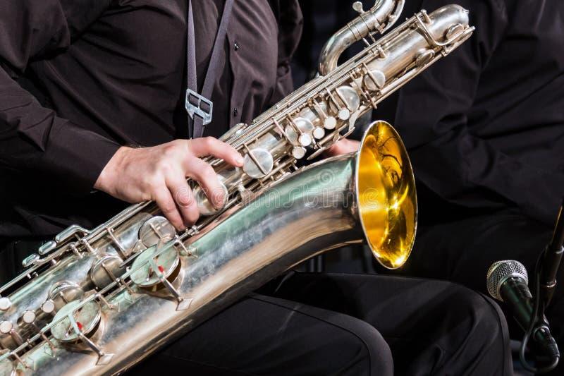 Das Baritonsaxophon liegt auf dem Knie des Musikers in einem schwarzen Hemd und in der Hose Die rechte Hand liegt auf einem hölze lizenzfreie stockfotografie