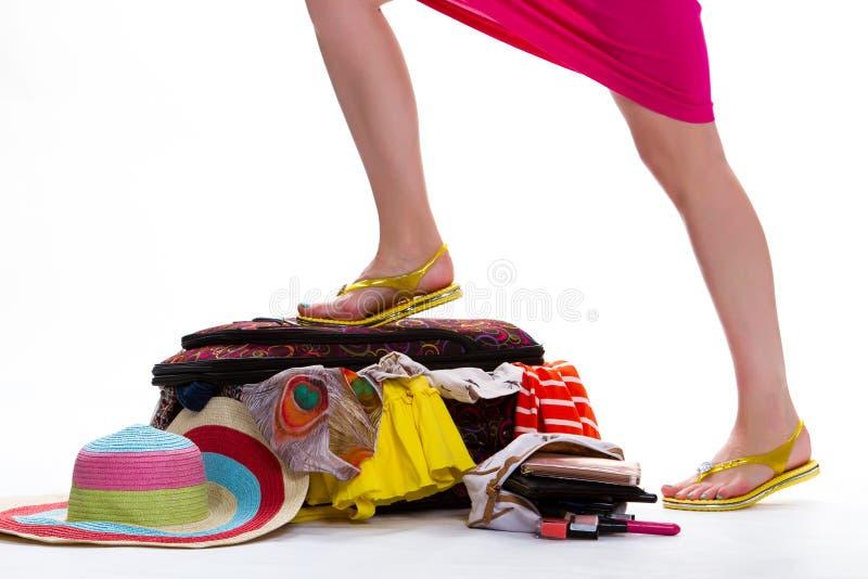 Das Bein der Frau auf gefülltem Koffer lizenzfreies stockfoto