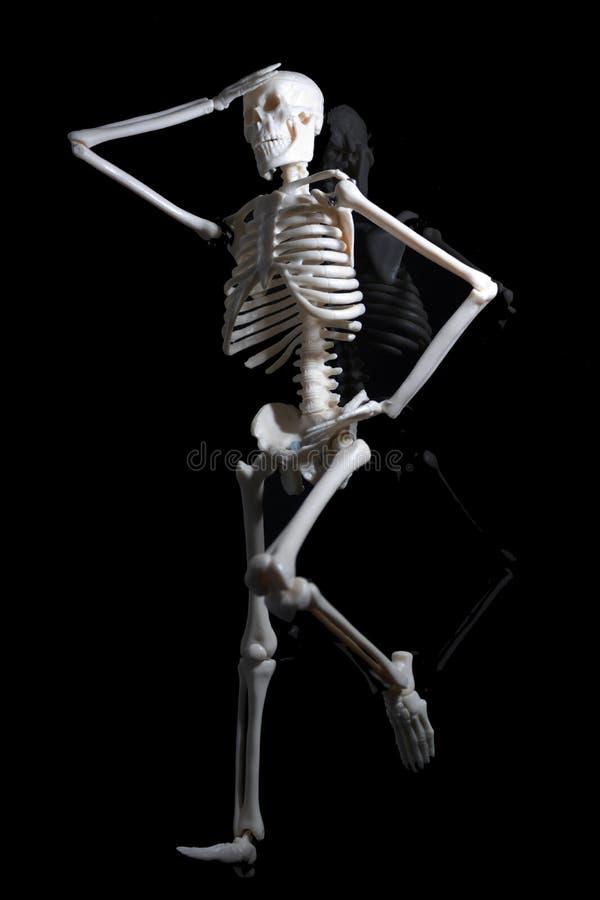 Das besorgte Skelett auf der schwarzen Reflexionsebene stockbilder
