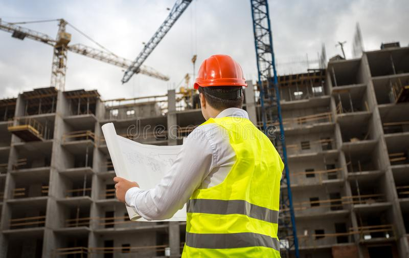 Das Bild der hinteren Ansicht des Bauingenieurs Pläne betrachtend und arbeitend streckt sich auf Baustelle stockfoto
