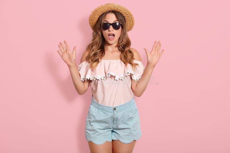 Das Bild der jungen Frau rosa Bluse, blauen Kurzschluss, Sonnenbrille und Sommerstrohhutstellung mit offenem Mund im Schock trage stockbilder