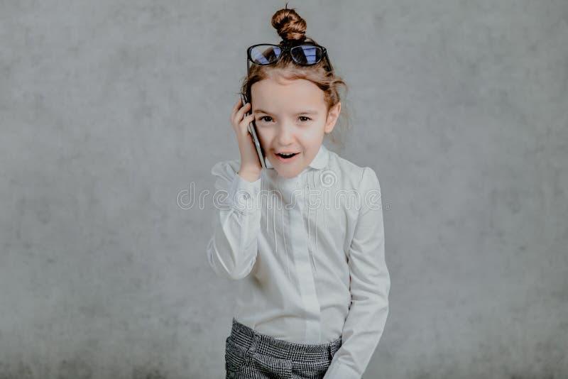 Das Bild emotionaler glücklicher Gesichter Kleine Schulmädchen Lächeln und reden mit einem Smartphone und zeigen stockfotografie