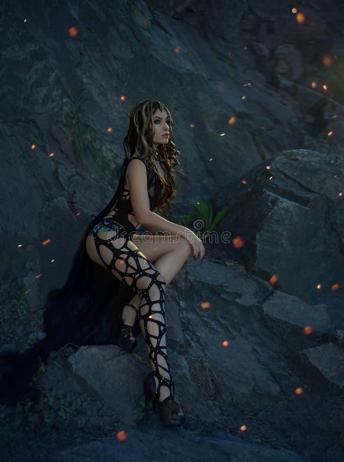 Das Bild von Gorgon Medusa, von Zopfhaar und von Gold schlängelt sich Ein Mädchen wirft nachts gegen den Hintergrund eines Felsen lizenzfreie stockfotos