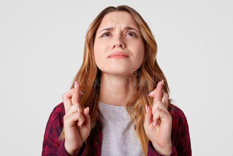 Das Bitten der Frau kreuzt Finger für gutes Glück, lässt traurigen Ausdruck, aufwärts fokussieren, lokalisiert über weißem Hinter stockfoto