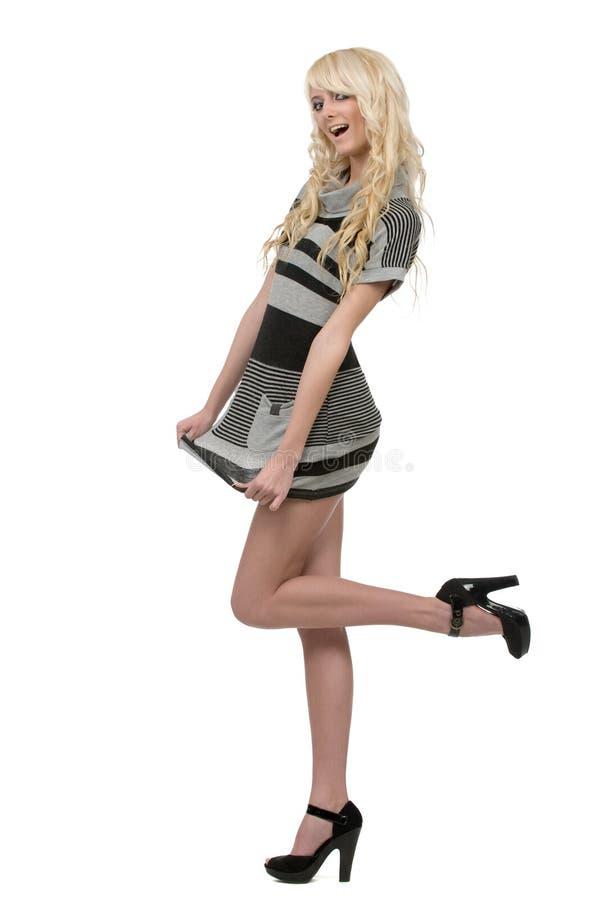 Das blonde Frauentragen striped Kleid und schwarzes hig lizenzfreie stockfotos