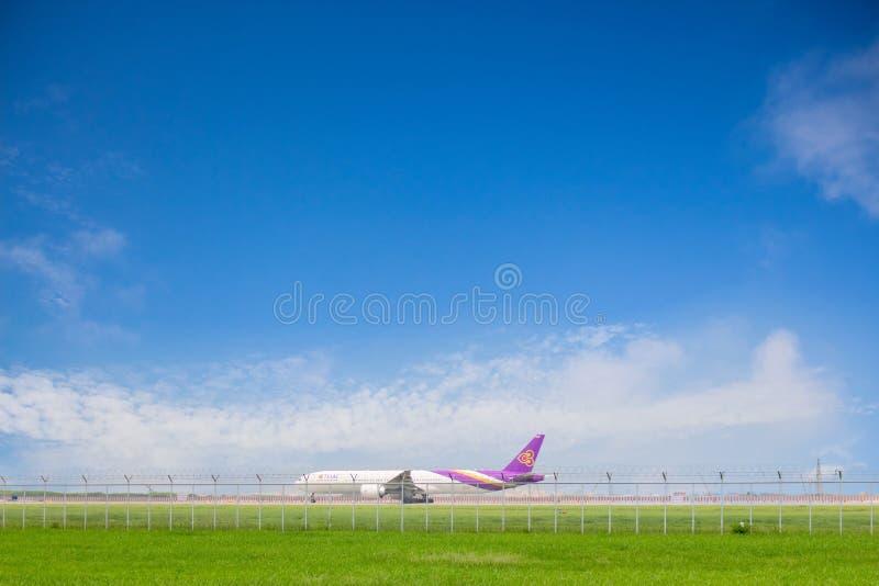 Das Boeing 777-300ER von Thai- Airwaysie vorbereitend für entfernen sich an Suvarnabhumi-Flughafen mit Hintergrund des blauen Him stockbild