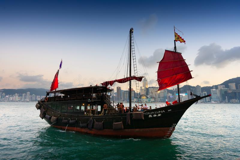Das Boot auf Victoria-Hafen mit Sonnenuntergang bei Hong Kong stockfotos