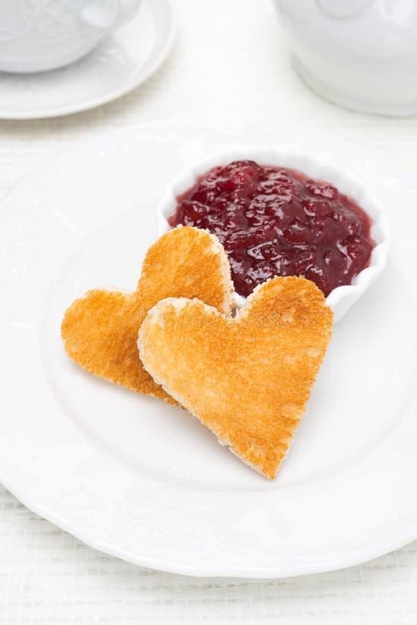 Das Brot mit zwei Toast in Form der Herzen und die Beere stauen in einer Schüssel stockfoto