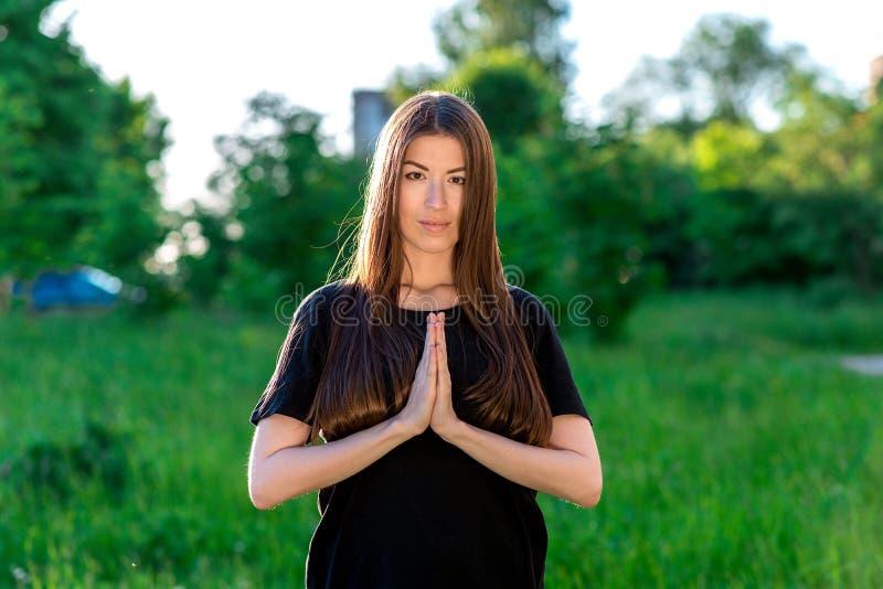 Das Brunettemädchen im Sommer draußen auf einer grünen Wiese Sie halten ihre Palmen im Gebet Emotional Blicke in stockbild