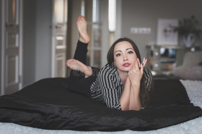 Das Brunettemädchen liegt auf einem großen Bett, auf ihrer Gesichtsruhe und ruhig lizenzfreie stockbilder