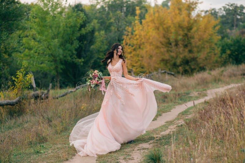 Das Brunettemädchen mit dem langen Haar wird glücklich in ein rosa Kleid mit einem Zug getanzt Eine Braut mit einem Blumenstrauß  stockfotografie
