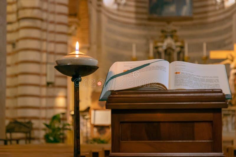 Das Buch der Liturgie der katholischen Kirche nahe der brennenden Lampe in stockfoto