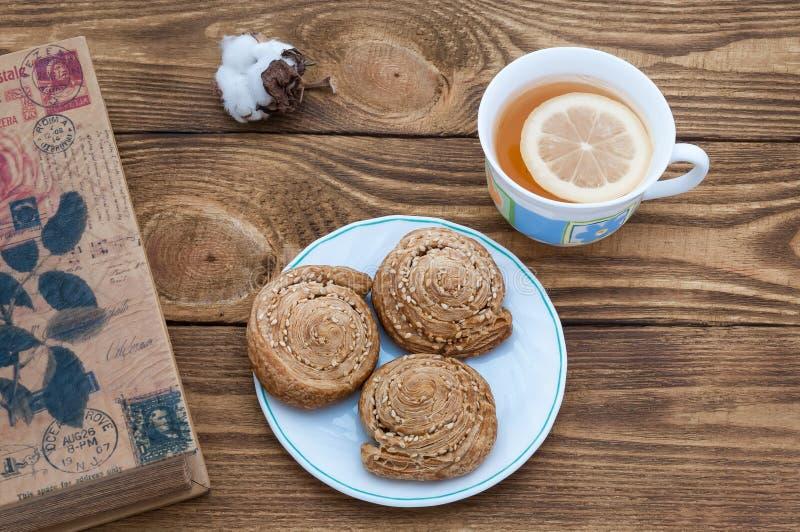 Das Buch, der Tee und die Kekse auf dem Tisch von dunklen Brettern stockfotos