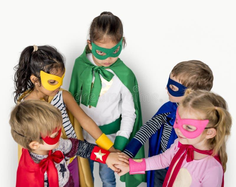 Das crianças do super-herói das mãos trabalhos de equipa junto imagens de stock