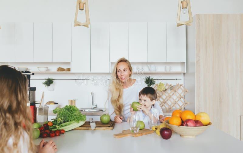 Das crianças felizes da mamã da família feliz cozinha de cozimento da casa do café da manhã fotografia de stock