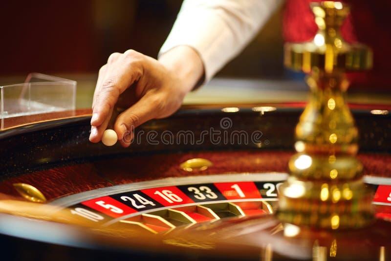Das Croupier hält einen Rouletteball in einem Kasino in seiner Hand stockbild