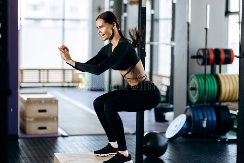 Das dünne dunkelhaarige Mädchen, das in der schwarzen Sportkleidung gekleidet wird, tut Hocken auf dem Kasten nahe bei der Sporta stockfoto