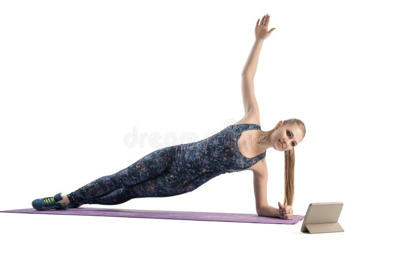 Das dünne Mädchen, das Übungen auf einer Matte tut, lokalisierte Ansicht lizenzfreies stockbild