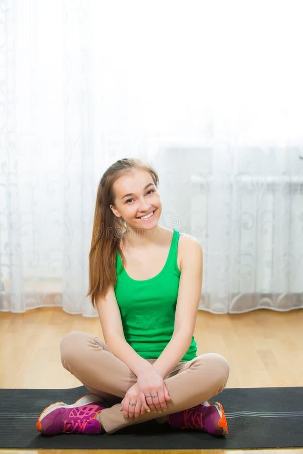 Das dünne Mädchensitzen entspannte sich auf Yogamatte nach ausarbeiten lizenzfreie stockfotos