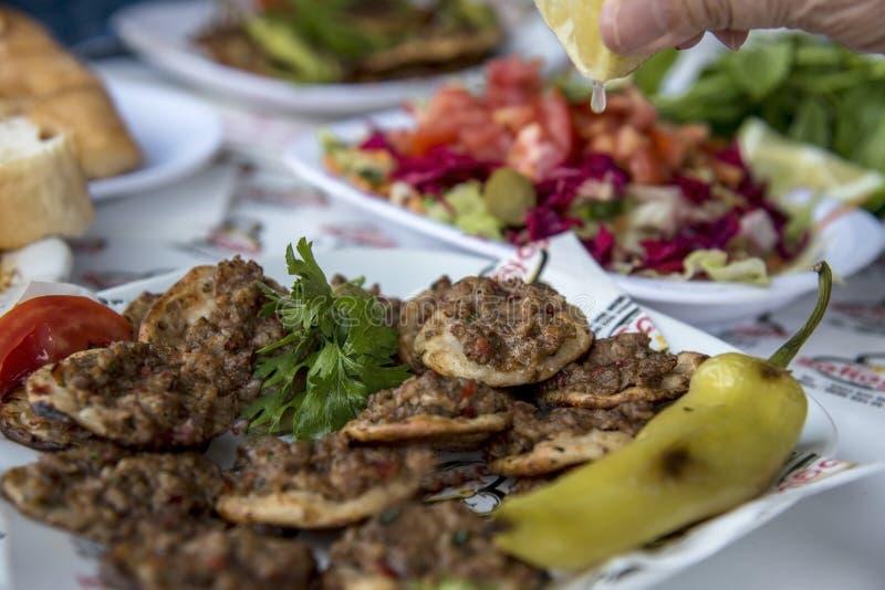 Das dünne türkische Pittabrot, das mit Hackfleisch und Zwiebeln mit gewürzter Zitrone in der Fußwurzelstadt bedeckt wird, schließ stockfotografie