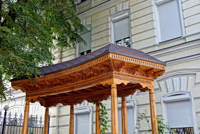 Das Dach einer hölzernen Pergola nahe der Wand des Hauses nahe dem grünen Baum lizenzfreie stockbilder