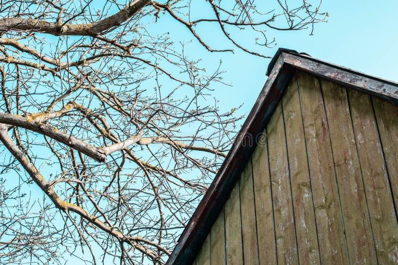 Das Dach eines alten Hauses auf dem Hintergrund des Himmels lizenzfreies stockfoto
