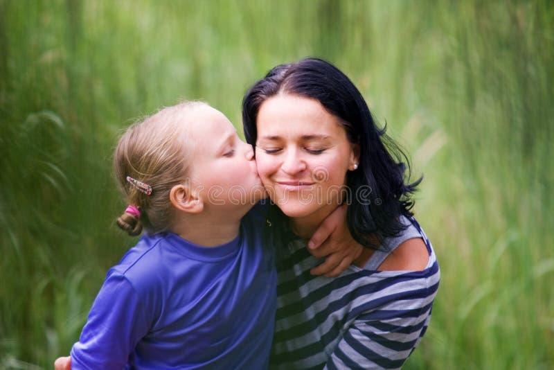 Das daugther küsst ihre Mutter stockfoto
