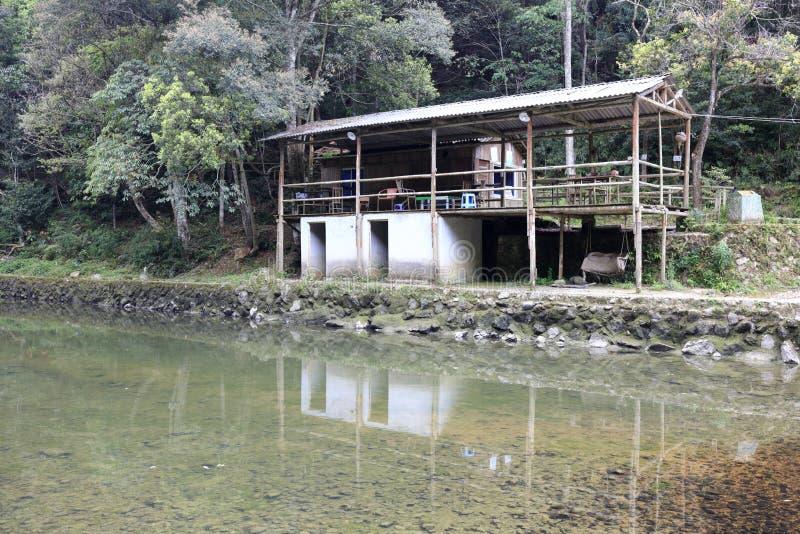 Das defekte einfache Haus durch Fluss stockbild