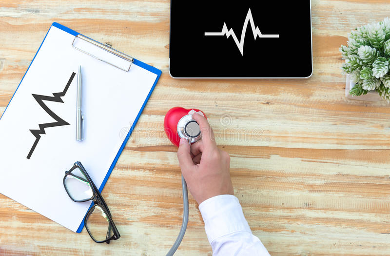 Das doctore mit einem medizinischen Stethoskopkontrollherzen lizenzfreies stockbild