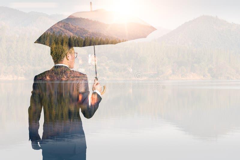 Das Doppelbelichtungsbild der Geschäftsmänner verbreiten Regenschirm während des Sonnenaufgangs, der mit Naturbild überlagert wir stockfotografie