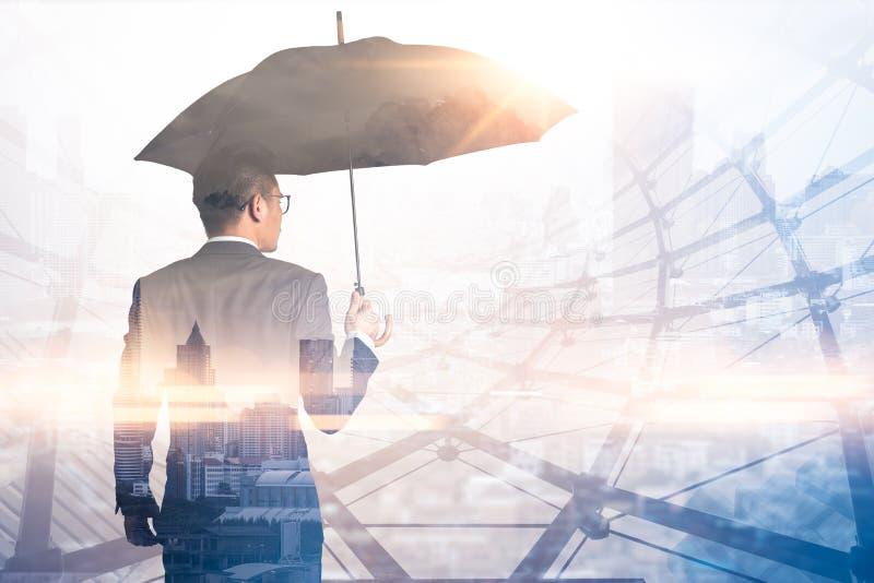 Das Doppelbelichtungsbild der Geschäftsmänner verbreiten Regenschirm während des Sonnenaufgangs, der mit Stadtbildbild überlagert stockfotos