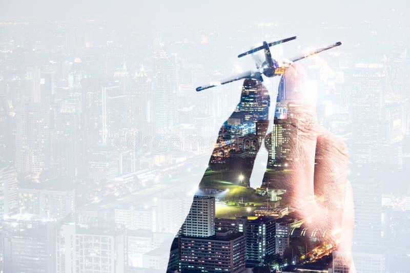Das Doppelbelichtungsbild des Flugzeugmodells an Hand überlagert mit Stadtbildbild das Konzept der Reise, Geschäft, Flugzeug, I lizenzfreies stockbild