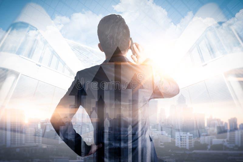Das Doppelbelichtungsbild des Geschäftsmannes, der einen Smartphone während des Sonnenaufgangs überlagert mit Stadtbild- und Gesc lizenzfreie stockfotografie