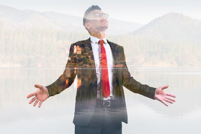 Das Doppelbelichtungsbild des Geschäftsmannes, der während des Sonnenaufgangs überlagert mit Waldbild sich entspannt Das Konzept  lizenzfreies stockbild