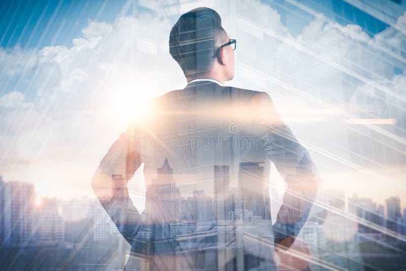 Das Doppelbelichtungsbild des Geschäftsmannes, der zurück während des Sonnenaufgangs überlagert mit Stadtbildbild steht Das Konze stockbilder