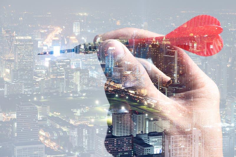 Das Doppelbelichtungsbild des Geschäftsmannes ein Pfeil overlaywith Stadtbildbild werfend das Konzept des Geschäfts, Dartscheibe, stockfotos