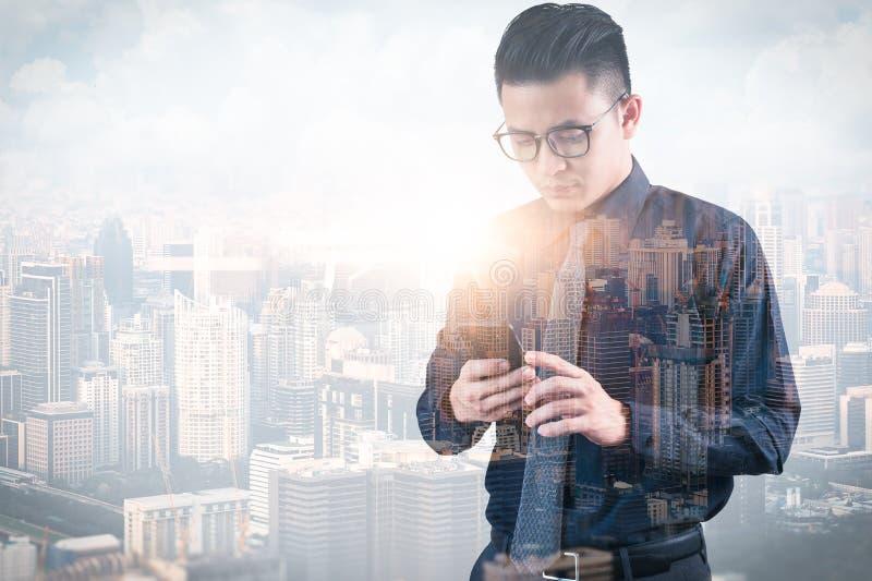 Das Doppelbelichtungsbild des Geschäftsmannes unter Verwendung eines Smartphone während des Sonnenaufgangs überlagert mit Stadtbi lizenzfreies stockfoto