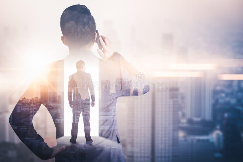 Das Doppelbelichtungsbild des Geschäftsmannes unter Verwendung eines Smartphone während des Sonnenaufgangs überlagert mit Stadtbi stockfoto