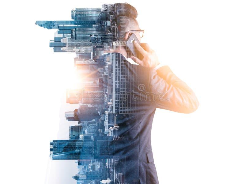 Das Doppelbelichtungsbild des Geschäftsmannes unter Verwendung eines Smartphone während des Sonnenaufgangs überlagerte mit Stadtb lizenzfreie stockbilder