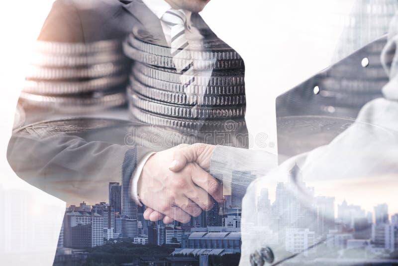 Das Doppelbelichtungsbild des Geschäftsmannhändeschüttelns mit einem anderen während der Sonnenaufgangüberlagerung mit Münzenstap lizenzfreie stockfotos