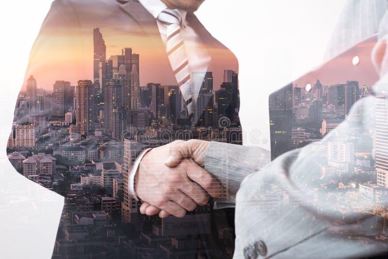 Das Doppelbelichtungsbild des Geschäftsmannhändeschüttelns mit einem anderen während des Sonnenaufgangs überlagerte mit Stadtbild lizenzfreie stockbilder